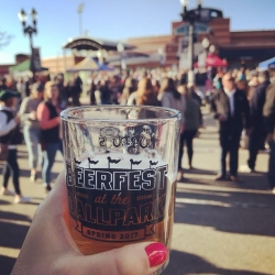"a hand holding a ""Beerfest in the Ballpark"" glass with the lugnuts stadium in the background"