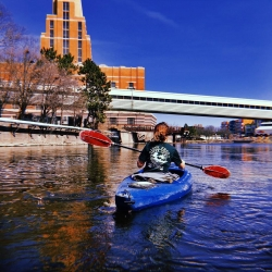a kayaker on the grand river with the accident fund building in the background